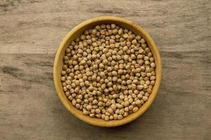 bunch of chickpeas in bowl on old wooden background
