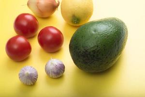 Vista aérea closeup guacamole dip ingredientes en tabla de cortar amarilla foto
