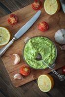 Guacamole on wooden table surrounded by its ingredients photo