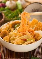singapore laksa curry noodles with plenty of raw ingredients as