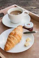 Croissant and coffee on wood background