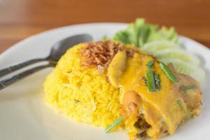 Biryani chicken yellow on a white plate.