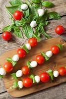 deliciosa merienda saludable antipasti caprese, brochetas con mozzarella albahaca y foto