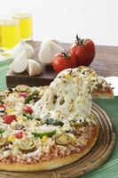 Delicious Pizza with Vegetables surrounding it in setting. photo