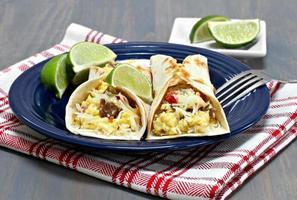 Dos tacos de desayuno con chorizo, huevos y pimientos.