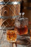 Glass of whiskey with ice and decanter photo