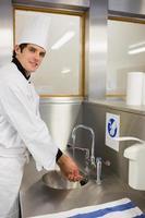 vrolijke chef-kok handen wassen