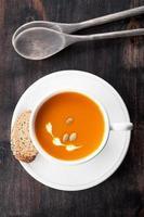 Pumpkin soup with pumpkin seeds in white mug