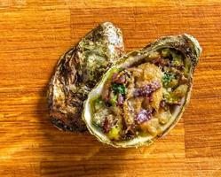Salad in oyster on a wooden background. photo