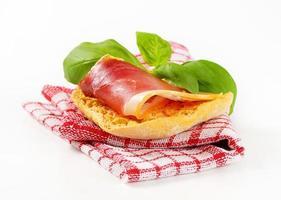 Slice of prosciutto on crispy bread photo
