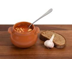 Soup in clay pot with bread and garlic on table