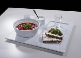 Ukrainian red borscht with salo sandwiches on ceramic tray photo