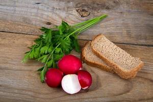 Fresh red radish parsley and bread on old wooden surface photo