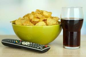 chips en un tazón, cola y control remoto de tv en la mesa foto