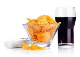 chips en un tazón, cola y control remoto de tv aislado en blanco foto