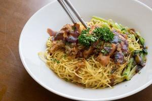 chinese noodle with sweet red pork on the table photo