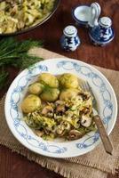 repollo nuevo guisado con champiñones, servido con papas nuevas (plato de verano polaco)