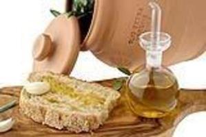 olio di oliva con fetta di pane e tagliere foto