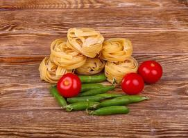 Pasta on the wooden background with tomato, pepper