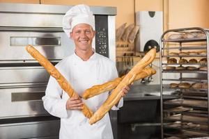 panadero sonriente sosteniendo tres baguettes