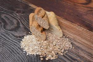 Bread and grains on wooden background photo