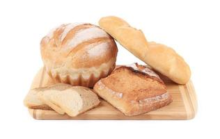 Various types of bread on cutting board. photo