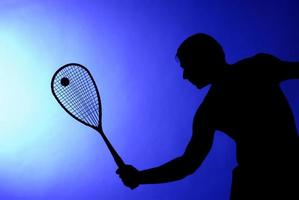 Man making a big swing in tennis game photo
