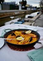 Seafood paella with glass of wine in seaside cafe,Spain