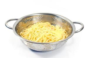 espaguetis cocidos frescos en colador de acero inoxidable aislado en blanco