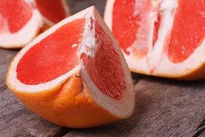 pieces of red grapefruit on the old wooden table closeup