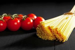 Raw pasta and tomatoes on black table