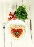 Cooked spaghetti carefully arranged in  heart shape on  wooden background
