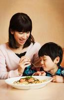 Mother and son happily eating spaghetti at the table