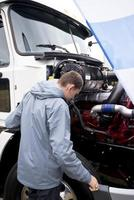 Truck driver checking operation engine semi truck with open hood