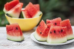 Watermelon pieces in two plates on a white wooden table