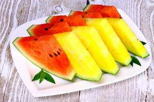 Red and yellow watermelon with mint on white plate