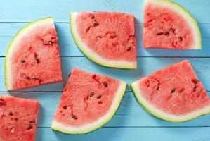 Watermelon slices on blue wood backdrop photo