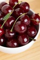 Sweet ripe cherry in bowl closeup photo