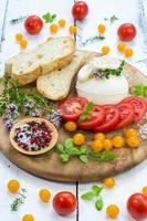 Fresh italian burrata and assorted tomatoes on a wooden plate