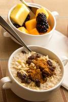 Fresh fruit and oatmeal with healthy toppings for breakfast photo