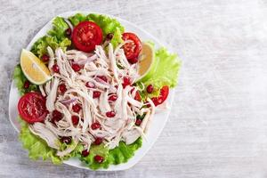 salad of white chicken meat with tomato and pomegranate seeds