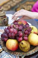 joven mujer sostiene uvas frescas cerca de la bandeja foto