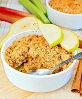 Crumble with pears and rhubarb on linen tablecloth photo