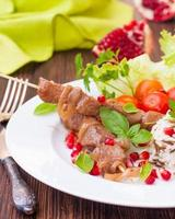 kebab and wild rice with fresh vegetables and pomegranate seeds
