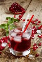 Fresh red juice cocktail with pomegranate seeds, mint and ice