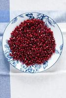pomegranate seeds on plate on white