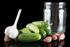 Gherkins in jar preparate for pickling on black photo