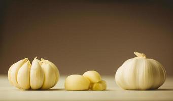 Garlic cloves and bulb on chopping board photo