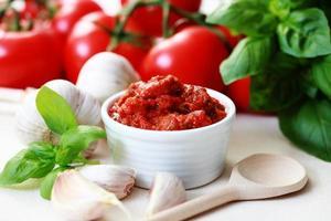 A white bowl of tomato sauce next to garlic
