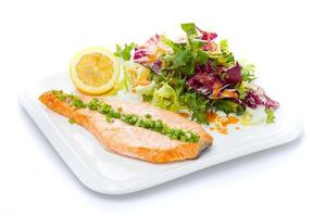 Salmon stake with green onion and salad mix photo